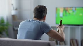 Bachelor watching football match supporting national team, drinking beer on sofa stock video footage