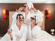 Bachelorette party fun females bathrobes champagne. Bachelorette party fun. Cheerful young females in sunglasses, bathrobes and turbans drinking champagne royalty free stock photo