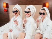 Bachelorette party fun females bathrobes champagne. Bachelorette party fun. Cheerful young females in sunglasses, bathrobes and towel turbans with champagne royalty free stock photography