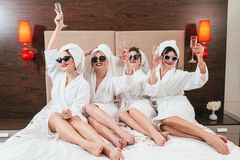 Bachelorette party fun females bathrobes champagne. Bachelorette party fun. Smiling females with champagne. Cheers. Sunglasses, bathrobes and turbans on. Bare stock photography