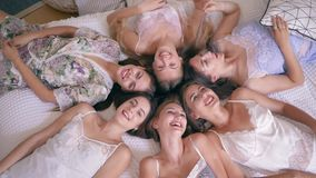 Bachelorette party, gorgeous smiling friends girl in silk pajamas lie on bed and look into the camera in apartment. Bachelorette party, gorgeous smiling friends stock video footage