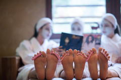 Bachelorette party in spa, girls with face mask reading magazine Royalty Free Stock Photography