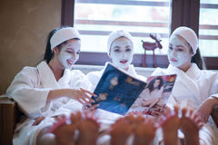 Bachelorette party in spa, girls with face mask reading magazine Stock Photos