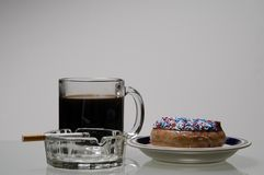 Bachlor's Breakfast. A bachlor's breakfast of coffee, cigarettes and doughnuts Stock Photography