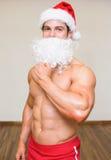 Bacho man with fake santa beard at the gym Royalty Free Stock Photos