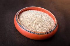 Bacia alaranjada de sementes saudáveis do Quinoa em um fundo de Brown imagens de stock royalty free