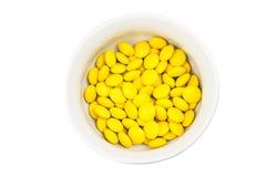 Bacia aérea da vista de doces de chocolate amarelos no fundo branco Imagem de Stock Royalty Free