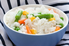 Bacia azul com arroz cozinhado com vegetal misturado imagens de stock
