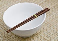 Bacia branca com chopsticks de madeira escuros Fotos de Stock