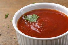 A bacia branca encheu-se com o molho de tomate caseiro com ervas Imagem de Stock