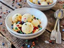 Bacia caseiro da luz do pêssego do gelado com chocolate colorido Fotos de Stock Royalty Free