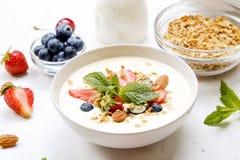 Bacia cerâmica do granola, ingredientes sortidos na tabela Café da manhã nutritivo saudável com iogurte do vegetariano, frutos cr foto de stock royalty free