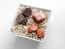 A bacia cerâmica do quadrado branco encheu-se com os feijões brancos, a salsicha, a salsicha de sangue e as despesas gerais vista fotografia de stock royalty free