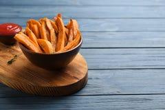 Bacia com as fritadas saborosos da batata doce no fundo de madeira fotos de stock royalty free