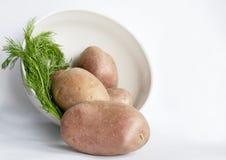 Bacia com batatas em um fundo branco Fotografia de Stock