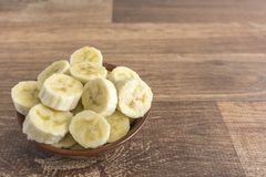 Bacia com fatias da banana no fundo de madeira foto de stock
