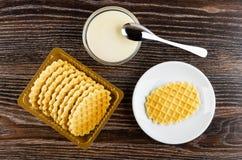 Bacia com leite condensado, colher de chá, caixa com cookies, cookie em uns pires na tabela de madeira Vista superior foto de stock royalty free