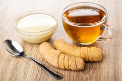 Bacia com leite condensado, croissant, copo do chá, colher na tabela fotografia de stock