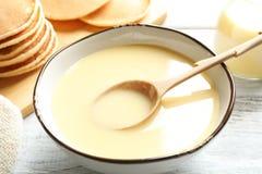 Bacia com leite condensado e colher na tabela foto de stock royalty free