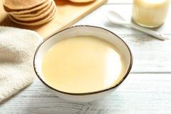 Bacia com leite condensado na tabela de madeira imagens de stock