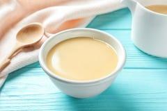 Bacia com leite condensado na tabela de madeira imagens de stock royalty free