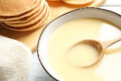 Bacia com leite condensado na tabela Produtos lácteos foto de stock royalty free