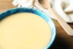 Bacia com leite condensado na tabela Produtos lácteos imagem de stock