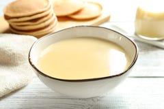 Bacia com leite condensado na tabela Produtos lácteos fotografia de stock royalty free