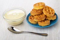 Bacia com leite condensado, os waffles redondos em uns pires azuis e a colher na tabela imagem de stock
