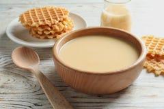 Bacia com o leite condensado servido na tabela, close up imagens de stock
