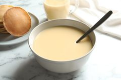 Bacia com o leite condensado servido na tabela de mármore, close up fotografia de stock