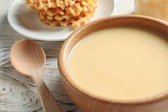 Bacia com o leite condensado servido na tabela Produtos lácteos imagem de stock