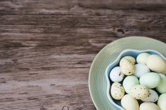 Bacia com os ovos da páscoa coloridos na placa azul, fundo de madeira fotografia de stock royalty free