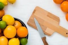 Bacia com tipos diferentes de citrinos inteiros: as laranjas, as toranjas, os cais e os limões, e esvaziam a placa de madeira com Fotografia de Stock Royalty Free