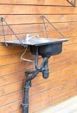 Bacia com um torneira instalado originalmente por correntes na parede exterior da casa Imagem de Stock