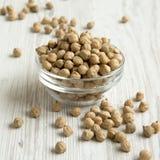 Bacia completa de grãos-de-bico secados em uma tabela de madeira branca, vista lateral Close-up fotografia de stock royalty free