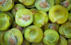 Bacia completamente de tipos diferentes das ameixas na grama verde saudável Imagem de Stock