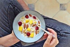 Bacia da farinha de aveia com bagas Menina que come o pequeno almoço Foto de Stock Royalty Free