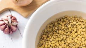 Bacia da lentilha com água ao lado da cebola e do alho imagem de stock