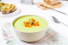 A bacia da sopa de creme das ervilhas verdes com cenoura cozida e microgreen brotos na tabela de madeira branca servida Alimento  fotos de stock royalty free