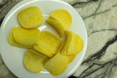 Bacia das microplaquetas de batata no branco fotos de stock