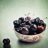 Bacia de cerejas no estilo do vintage Foto de Stock