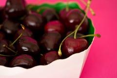 Bacia de cerejas pretas no fundo cor-de-rosa brilhante Imagem de Stock