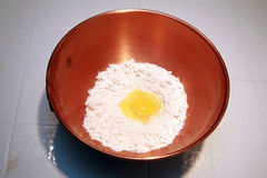Bacia de cobre com farinha e um ovo Imagens de Stock