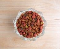 Bacia de comida de gato genérica seca na parte superior contrária de madeira Fotos de Stock