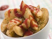 Bacia de cunhas da batata e de ketchup de tomate Fotos de Stock