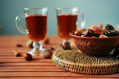 Bacia de datas secadas na tabela de madeira velha com chá Imagem de Stock Royalty Free