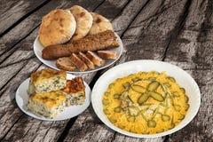 Bacia de ensalada russa com fatias do Baguette e de Loafs do pão de Pitta com a torta do queijo dos espinafres ajustada na tabela Imagens de Stock