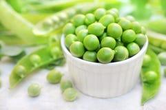 Bacia de ervilhas verdes colhidas frescas no fundo das vagens imagens de stock