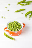 Bacia de ervilhas verdes frescas na tabela branca Imagens de Stock